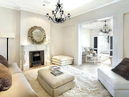 black chandelier in an all white living room off walls with cream rug and furniture beige