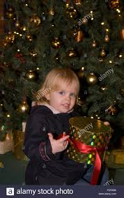 2 year old girl sitting around the christmas tree with presents, Bordon, Hampshire, UK. presents