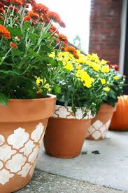 charm up the ordinary clay pots into these diy stenciled pots using painting stencil visit diy candy to know more