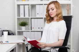 woman office furniture. Stock Photo - Woman In White Shirt Reading Red Book At Office Desk. Modern Interior. Concept Of Free Time Importance. Furniture