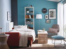 a living room with a dark orange sofa bed made with beige bed linen and bedroom furniture in ikea
