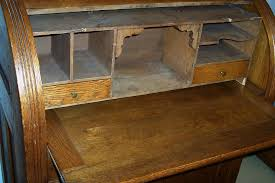 this is a solid oak antique cylinder roll top desk has a slide out writing surface also includes removable organizer