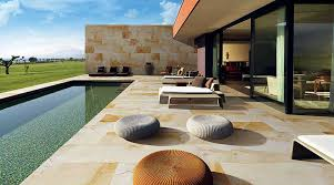 a stunning modern villa with exterior sandstone effect thin tiles to the pool and exterior patio
