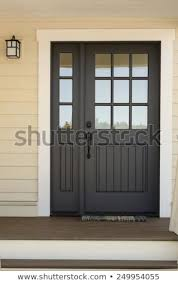 close up of black front door on house with yellow exterior siding