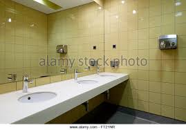 large public bathroom. public restroom with a row of lavatories in front large mirror - stock image bathroom i