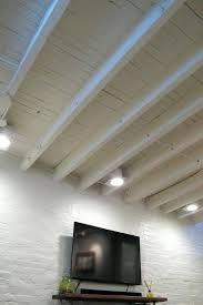 low ceiling lighting solutions cozy chic basement with exposed painted joists wood tile floors unfinished basement