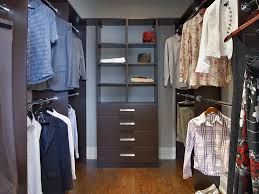 chocolate pear walk in closet with clothes hanging and shelf and drawer tower with flat fronts