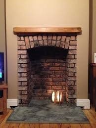 image result for wood burning stove in brick fireplace