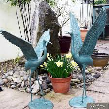 pair of tall garden cranes wings outstretched gold verdigris