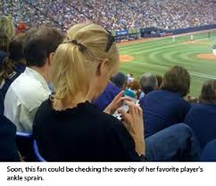 woman using cell phone at baseball game