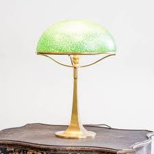 An Art Nouveau Brass Table Lamp With An Iridescent Glass Dome Shade