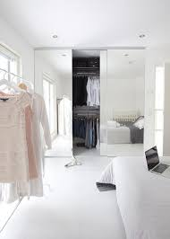 sun filled bedroom features a bed dressed in a white and gray quilt situated across from a freestanding clothes rack placed in front of a window alongside a