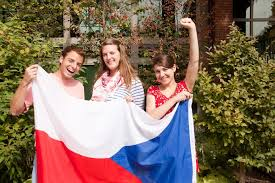"""Paul Lemieux, Rebecca """"Becca"""" Peterson-Perry, and Hilary Leonard,  sophomores, all took a gap year before coming to Whitman. They hold  Hilary's flag from the Czech Republic where she spent her gap year. –"""