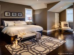 A warm and cozy bedroom with dark hardwood floors and brown paint. The  white ceiling