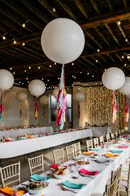 industrial wedding venue decorated with fairy light and giant balloons with colourful tissue tels