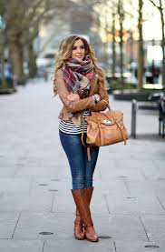 we see brown leather jacket that is updated with tartan wrap scarf black white striped top and blue skinnies tucked in brown leather boots