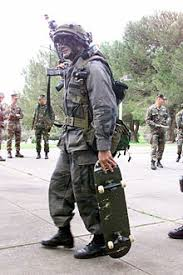 Soldier carrying a skateboard during military exercise