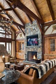 great room with a large flat screen tv above the fireplace in a douglas fir woodhouse timber frame mountain home