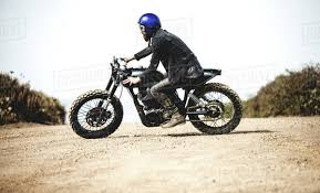 side view of man wearing blue open face crash helmet and goggles riding cafe racer motorcycle on a dusty dirt road