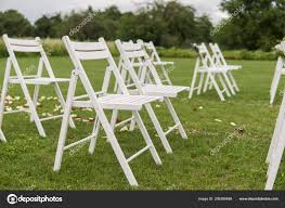 white wedding chairs decorated with fresh flowers on a green grass empty wooden chairs for