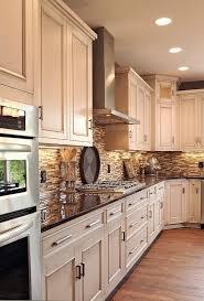 light cabinets dark counter oak floors neutral tile black splash cabinet and lighting