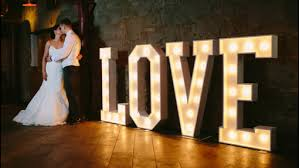 lighting letters. couple standing with the light up love letters lighting letters