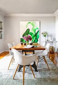 elegant dining e with large art a wood table and white eames chairs
