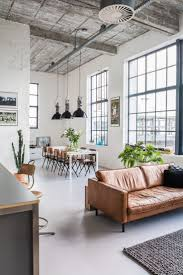 industrial style dining room lighting. leather cream sofa with black pillow glossy pendant light white stained dining table industrial living room decorative plants brown wooden style lighting t