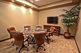 interior round glass meeting table and brown leather swivel chairs on brown carpet connected by