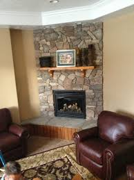 furniture grey stone fireplace with brown wooden mantel shelf connected by brown leather chair on