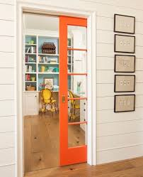 sliding barn doors had their moment now it s time to revamp with this glass paned bright orange sliding door that is the perfect divider for any home