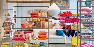 pillows in bright hues line the shelves of abc home s new brooklyn location