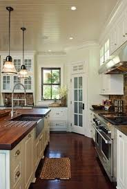 bead board ceiling and dark hardwood in kitchen white cabinets with butcher block countertops the sink