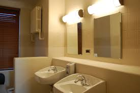 double bathroom wall mounted light fixtures above wall mirror and vanity plus brown wall interior color decor ideas