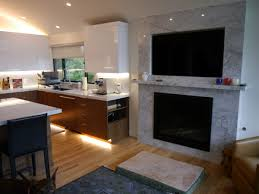 white acrylic upper cabinets with walnut lower cabinets marble countertops and backsplash built in gas fireplace and television