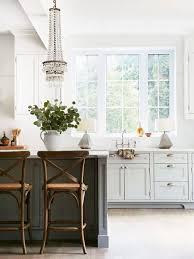 rustic chic kitchen with crystal chandelier and table lamps beside the sink on thou swell