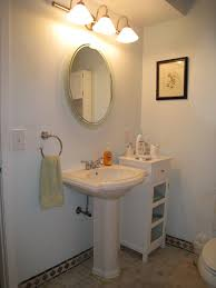 outstanding rounded wall mount mirror over white pedestal sink beside white cabinet in white small powder