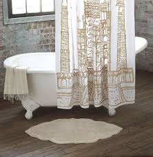 gold and white Taj Mahal shower curtain in brick bathroom with wood floors.