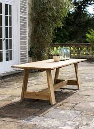 flared teak indoor and outdoor dining table with tapered legs and a soft wood grain