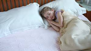 A Little Girl Sleeping In Her Bed Waiting For The Tooth Fairy To
