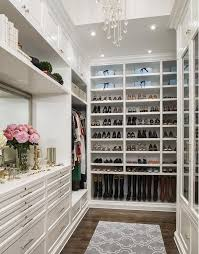 custom closets for women. This Elegant White Closet Has Customized Storage For Boots, Flats And Heels On One Long Wall. A Dresser With Large Gilded Mirror Sits The Far Wall, Custom Closets Women G