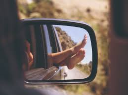 mirror reflection.  Mirror A Person Sticking Their Feet Out Of A Car Window From The Perspective  Rear With Mirror Reflection