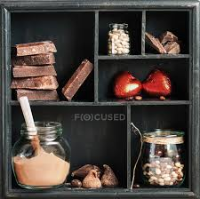 wooden rustic box with various chocolates on shelves stock photo