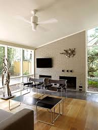example of a midcentury modern living room design in dc metro with a standard fireplace and