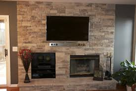 this stacked stone fireplace was designed with a built in audio system and flat screen tv