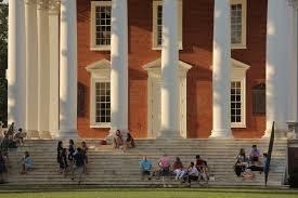 students standing at base of columns at dusk