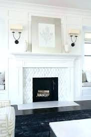 white stone fireplace wall white fireplace mantel black sconces on white board and batten fireplace wall