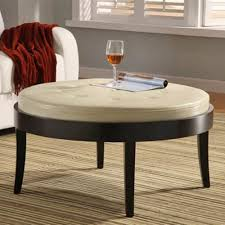 round cocktail ottoman table with white leather tufted top and black wooden legs for small living room spaces ideas