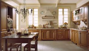 classic italian kitchen design with 3 piece dining set under chandelier and copper kitchen cookware also utensils hanging on wall holder