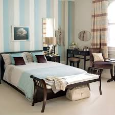 bedroom black wooden bed with white blue bed sheet combined with brown wooden bench and